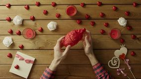 Il giovane esamina il cuore umano di plastica dalla tavola di legno, vista superiore stock footage