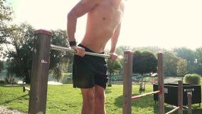Il giovane fa i vari esercizi di peso corporeo alla barra orizzontale video d archivio