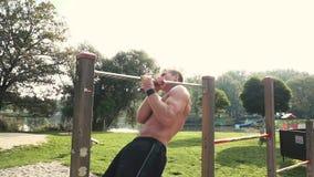 Il giovane fa i vari esercizi di peso corporeo alla barra orizzontale stock footage