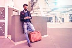 Il giovane felice con lo smartphone - adatti il tipo dei pantaloni a vita bassa che per mezzo del telefono immagine stock libera da diritti