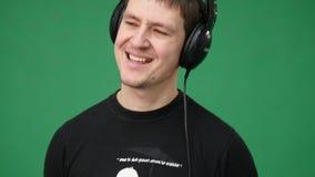 Il giovane felice in cuffie che ballano ed ascolta musica su fondo verde video d archivio
