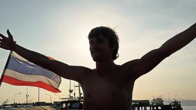 Il giovane felice solleva le sue mani al rallentatore sul pilastro del mare accanto alla bandiera tailandese Il sole è brillante  video d archivio