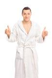 Il giovane felice in un accappatoio bianco che dà due pollici su isola fotografia stock libera da diritti