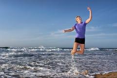 Il giovane felice vola con il telefono mobile Fotografie Stock Libere da Diritti