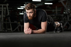 Il giovane forte uomo concentrato di sport fa la plancia fotografie stock libere da diritti