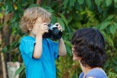 Il giovane fotografo con una macchina fotografica spara alla sua madre Immagini Stock Libere da Diritti