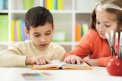 Il giovane fratello e la sorella imparano come leggere a casa Immagini Stock