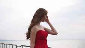 Il giovane fronte grazioso della ragazza nel profilo, sta godendo della vista sul mare nel giorno di estate nuvoloso video d archivio