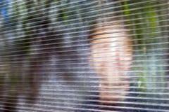Il giovane fronte sorridente vago dietro Dusty Fluted, vetro costolato o il chiaro policarbonato ha ondulato lo strato Online ano fotografia stock