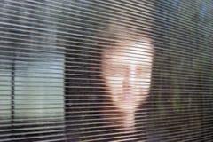 Il giovane fronte sorridente vago dietro Dusty Fluted, vetro costolato o il chiaro policarbonato ha ondulato lo strato Online ano immagine stock libera da diritti