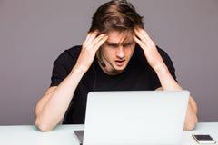 Il giovane gamer che gioca la cuffia d'uso del video gioco e perde GA Fotografia Stock Libera da Diritti