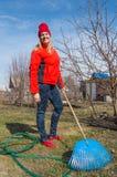 Il giovane giardiniere femminile affascinante sta nel suo giardino sul fondo del cielo blu, gli strumenti di giardino del primo p fotografie stock