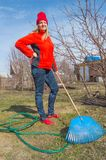 Il giovane giardiniere femminile affascinante sta nel suo giardino sul fondo del cielo blu, gli strumenti di giardino del primo p fotografie stock libere da diritti