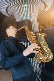 Il giovane gioca un sassofono dello strumento musicale immagini stock libere da diritti