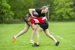 Il giovane giocatore femminile di rugby su backround verde fotografie stock