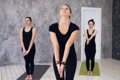 Il giovane gruppo allegro del trio di ragazze sta praticando gli esercizi di yoga nello studio Fotografia Stock Libera da Diritti