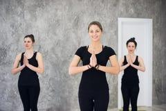 Il giovane gruppo allegro del trio di ragazze sta praticando gli esercizi di yoga nello studio Fotografia Stock