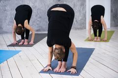 Il giovane gruppo allegro del trio di ragazze sta praticando gli esercizi di yoga nello studio Fotografie Stock Libere da Diritti