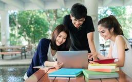 Il giovane gruppo di studenti si consulta con le cartelle della scuola, computer portatile immagine stock
