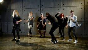 Il giovane gruppo fa la prestazione di break-dance vicino alla parete video d archivio