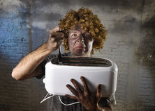 Il giovane ha fulminato la prova di ottenere il pane tostato dal tostapane con il coltello che subisce l'infortunio domestico Fotografie Stock