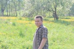 Il giovane ha girato indietro, camminando lungo un prato della molla con giovane erba fertile Sparato in lampadina fotografia stock