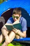 Il giovane ha letto un libro immagine stock