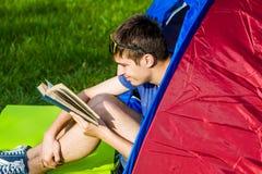 Il giovane ha letto un libro fotografie stock
