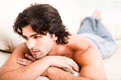 Il giovane immagina ponendo sul sofà Immagine Stock