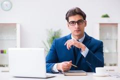 Il giovane impiegato bello dell'uomo d'affari che lavora nell'ufficio allo scrittorio Fotografie Stock Libere da Diritti