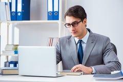 Il giovane impiegato bello dell'uomo d'affari che lavora nell'ufficio allo scrittorio Fotografia Stock