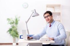 Il giovane impiegato bello dell'uomo d'affari che lavora nell'ufficio allo scrittorio Fotografia Stock Libera da Diritti