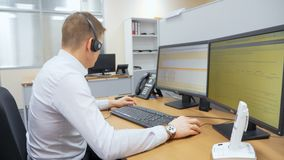 Il giovane impiegato lavora davanti agli schermi di computer in ufficio archivi video