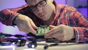 Il giovane ingegnere sta collaudando un circuito nell'ambito della luce intensa video d archivio