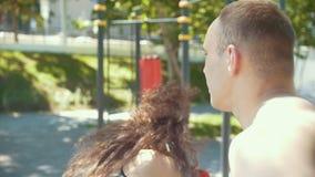 Il giovane insegna ai bei colpi di pugilato della donna all'aperto al giorno soleggiato, rallentatore stock footage