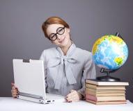 Il giovane insegnante con i libri, il globo ed il taccuino. Immagine Stock