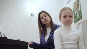 Il giovane insegnante femminile con poca ragazza sveglia controlla l'orecchio per vedere se c'? musica archivi video