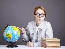 Il giovane insegnante in vetri con i libri ed il globo Fotografia Stock