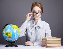 Il giovane insegnante in vetri con i libri ed il globo Fotografie Stock