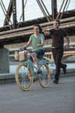 Il giovane insegue la ragazza sulla bici Fotografia Stock