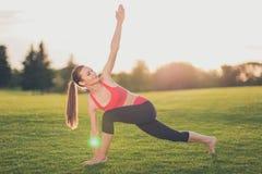 Il giovane istruttore della donna di sport sta facendo l'allungamento all'aperto nello sprin Immagine Stock