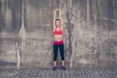 Il giovane istruttore di sportwoman sta facendo l'allungamento all'aperto nella città Fotografie Stock Libere da Diritti