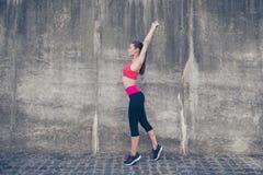 Il giovane istruttore di sportwoman sta facendo l'allungamento all'aperto nella città Immagine Stock