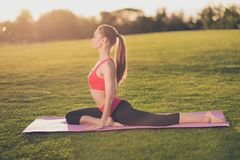 Il giovane istruttore di yoga sta facendo l'allungamento all'aperto nel parco di primavera Fotografia Stock Libera da Diritti