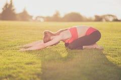 Il giovane istruttore di yoga sta facendo l'allungamento della menzogne all'aperto in primavera Fotografia Stock