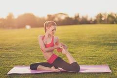 Il giovane istruttore di yoga sta facendo l'allungamento della seduta all'aperto nello spri Immagini Stock Libere da Diritti