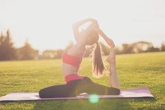 Il giovane istruttore di yoga sta facendo l'allungamento della seduta all'aperto nello spri Immagine Stock