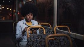 Il giovane libro di lettura afroamericano del passeggero o della donna che si siede nel trasporto pubblico, steadicam ha sparato  archivi video