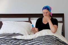 Il giovane malato di cancro in un foulard riposa a letto con la nausea ed esamina le pillole con repulsione fotografia stock libera da diritti