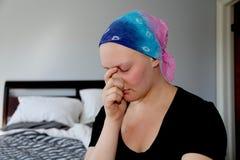 Il giovane malato di cancro in un foulard tiene la testa in mani con lo sforzo immagini stock libere da diritti